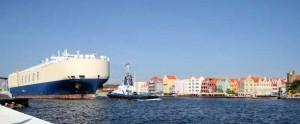 Ein Schlepper zieht das große Schiff vorbei an den Häusern der Altstadt vom Hafen hinaus ins offene Meer